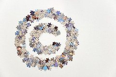 Large copyright sign made of colorful jigsaw puzzle pieces, isolated on a white background in landscape mode and with plenty of white space on the right side.